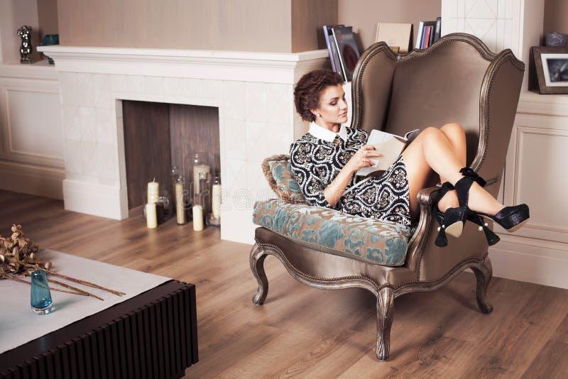 Reiche freche Frau des schönen Brunette im eleganten Kleid, das auf einem Stuhl in einem Raum mit klassischem trinkendem Innenwei lizenzfreies stockbild