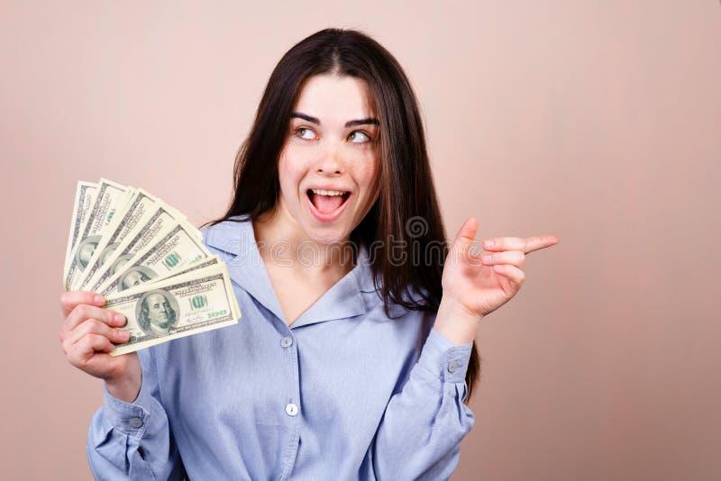 Reiche junge Frau mit Geld zeigend auf freien Raum stockfotos