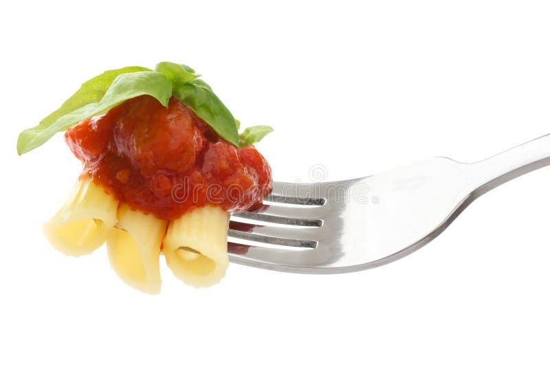 Reiche Tomatensauce, Teigwaren und Basilikum auf einer Gabel stockbilder