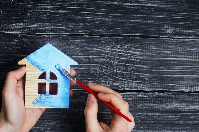 Reichen Sie Farben ein Haus zur blauen Farbe ein Konzept der Reparatur, Hobby, Arbeit Reparatur und Malerei von Holzhausfigürchen stockfoto