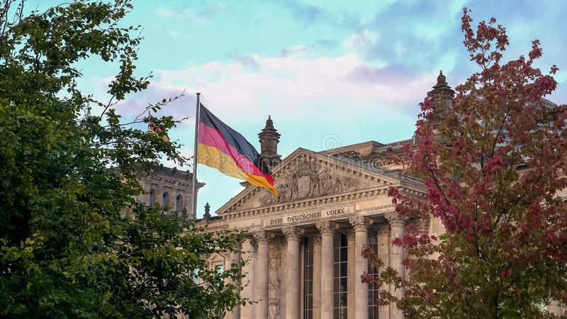 Reichstag and german flag framed by trees in berlin, germany royalty free stock image