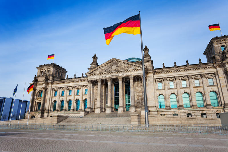 Reichstag facade view with German flags, Berlin. Reichstag facade view with German flags in Berlin, Germany royalty free stock images