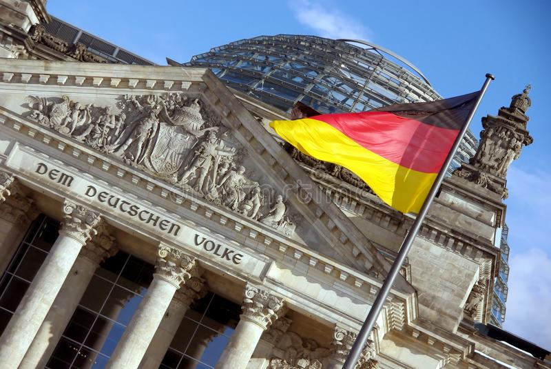 Reichstag with German Flag, Berlin, Germany (Bundestag). The Reichstag, Berlin, topped by the magnificent Norman Foster dome, with a fluttering German stock photo
