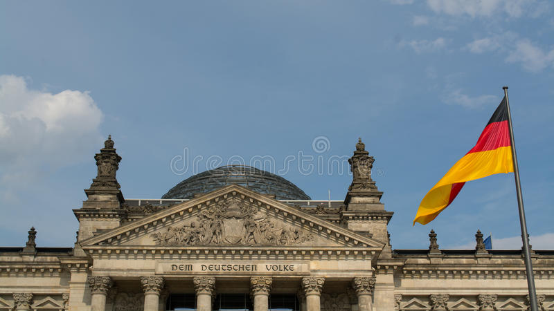 Reichstag with the german flag. The german flag in front of the Reichstag dome (german parliament building) in Berlin royalty free stock images