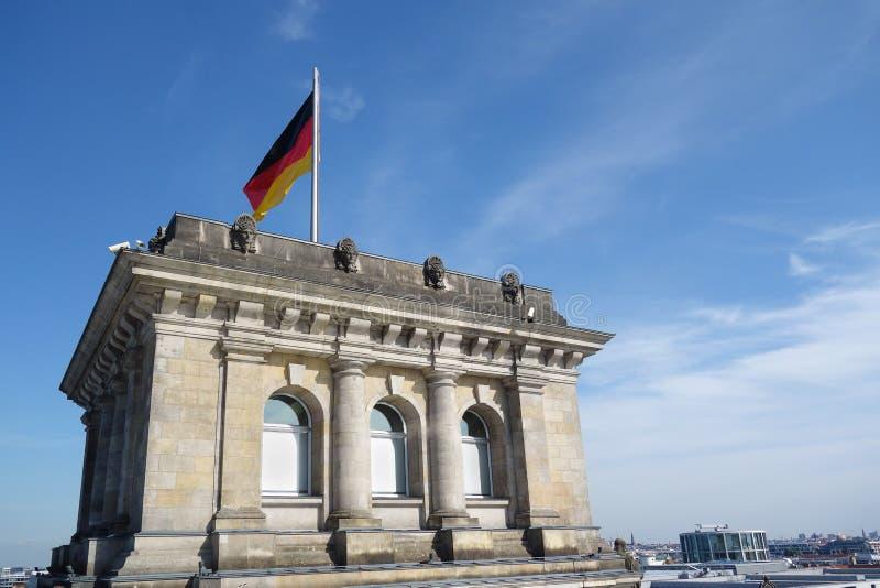Reichstagen med den tyska flaggan royaltyfri foto