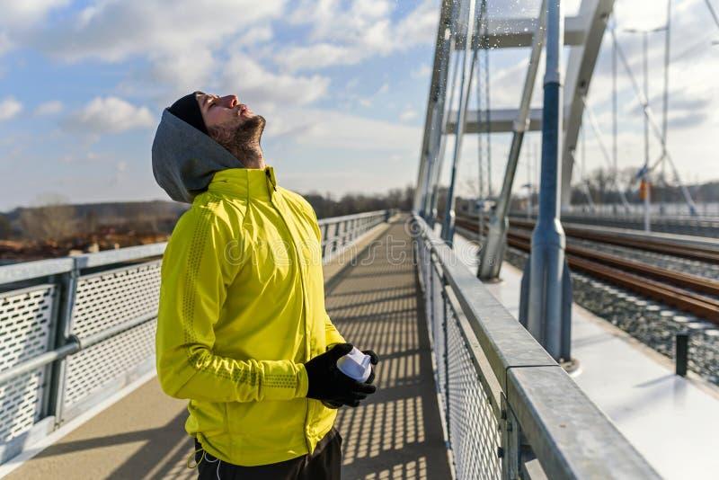 Reidratazione acqua bevente del giovane uomo dell'atleta durante l'esercizio all'aperto fotografie stock