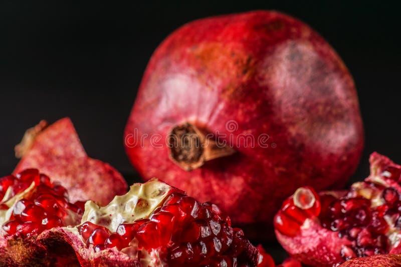 Reif; frische Granatapfelfrucht; auf schwarzem Hintergrund lizenzfreie stockfotos
