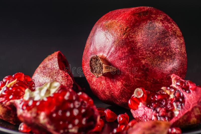 Reif; frische Granatapfelfrucht; auf schwarzem Hintergrund stockfotografie