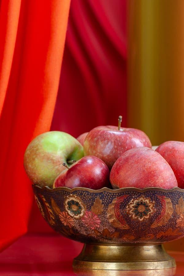 Reife Äpfel in einem Vase in der orientalischen Art auf einem stilvollen Hintergrund lizenzfreie stockbilder