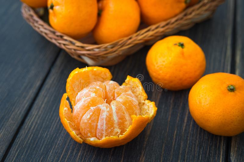 Reife abgezogene Tangerine und ein Weidenkorb von saftigen orange clemen stockbilder
