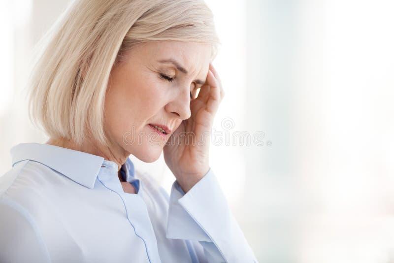 Reife alte Geschäftsfrau des müden Umkippens, die unter starkem chron leidet stockfotos
