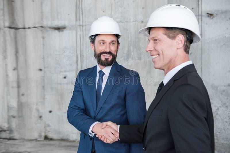 Reife Architekten in den Sturzhelmen, die Hände und das Lächeln rütteln stockfoto
