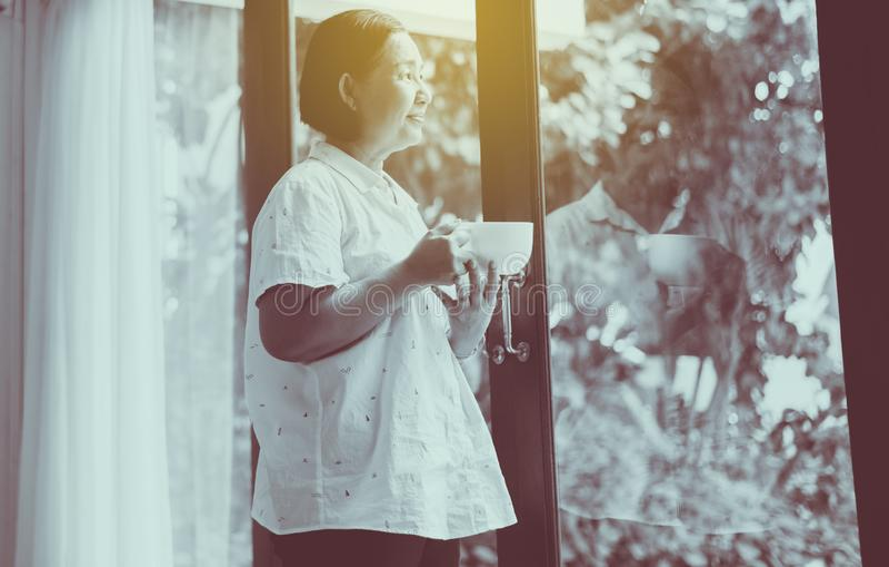 Reife asiatische Frau mit einer Tasse heißen Kaffee in der Nähe des Fensters am Morgen, glücklich und lächelnd,positives Denken,S stockfotos