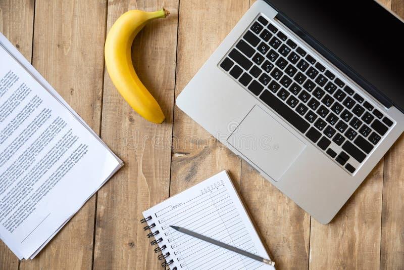 Reife Banane, Laptop und Papiere auf die Holztischoberseite lizenzfreie stockbilder