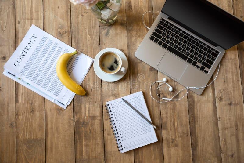 Reife Banane, Laptop und Papiere auf die Holztischoberseite stockfoto