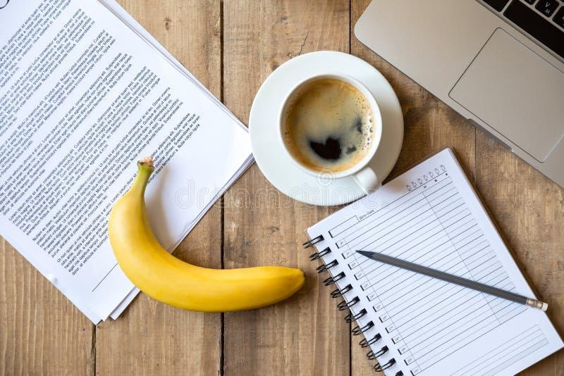 Reife Banane, Laptop und Papiere auf die Holztischoberseite stockfotos