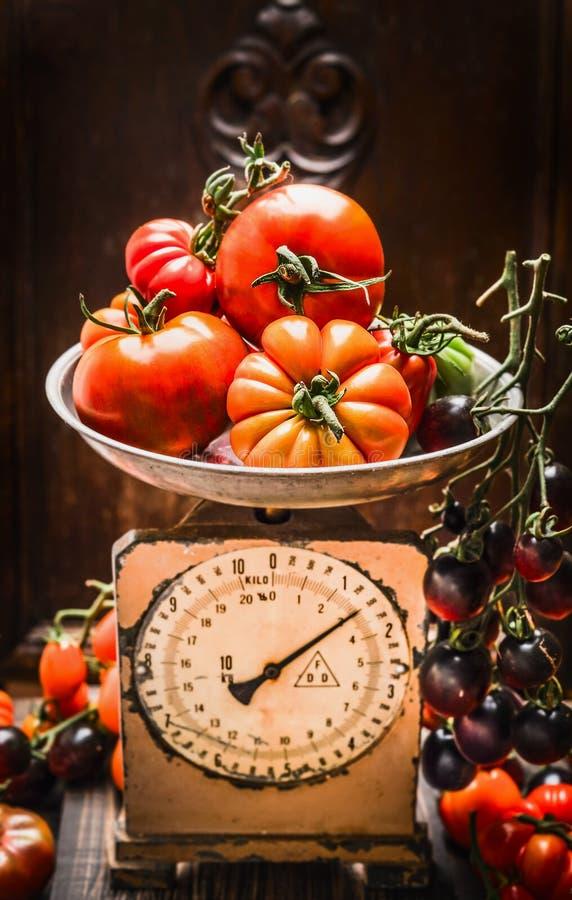 Reife Bauernhoftomaten auf Weinleseskalen, Küchenstilllebenszene stockfoto