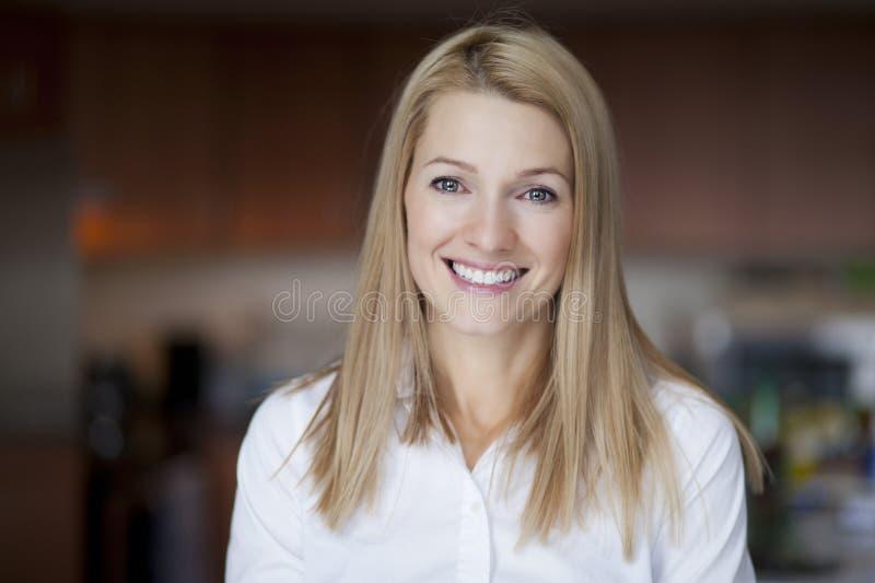 Reife blonde Frau lächelt an der Kamera stockfotografie