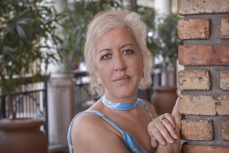 Reife blonde Frauen lehnen sich mit den Händen auf einer Backsteinmauer, die Kamera mit einem angenehmen Lächeln betrachtet stockfotografie