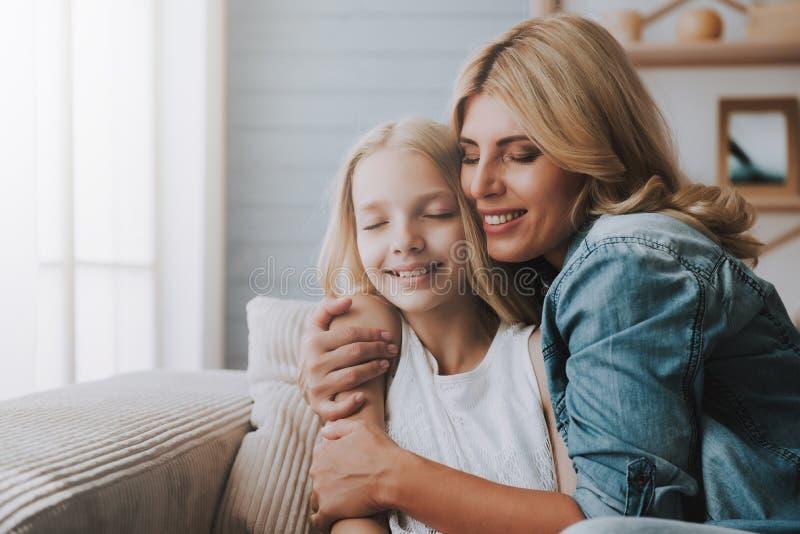 Reife Blondine, die Tochter umarmen Konzept der Versöhnung der Mutter mit Tochter lizenzfreie stockfotografie