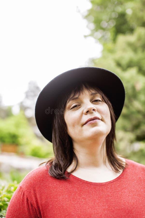 Reife Brunettefrau in tragendem Hut des grünen Gartens, lächelnd, freundliches Welkoming, Lebensstilleutekonzept lizenzfreie stockfotos