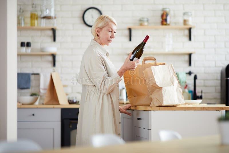 Reife Dame, die Papiertüten in der Küche auspackt lizenzfreie stockfotografie