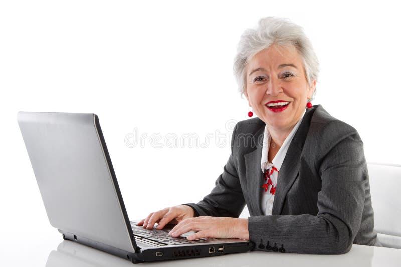 Reife Dame mit dem Laptop - lokalisiert auf Weiß lizenzfreie stockbilder