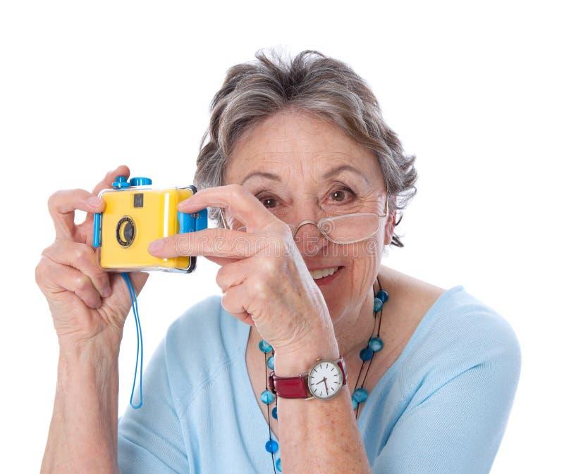 Reife Dame mit einer Kamera - ältere Frau lokalisiert auf weißem backgr lizenzfreie stockfotos