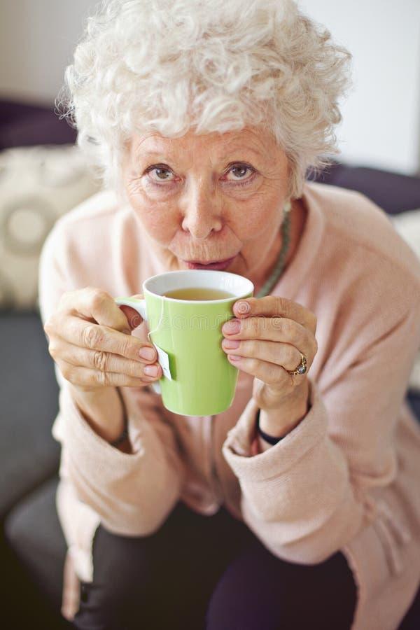Reife Dame zu Hause, die Tee trinkt