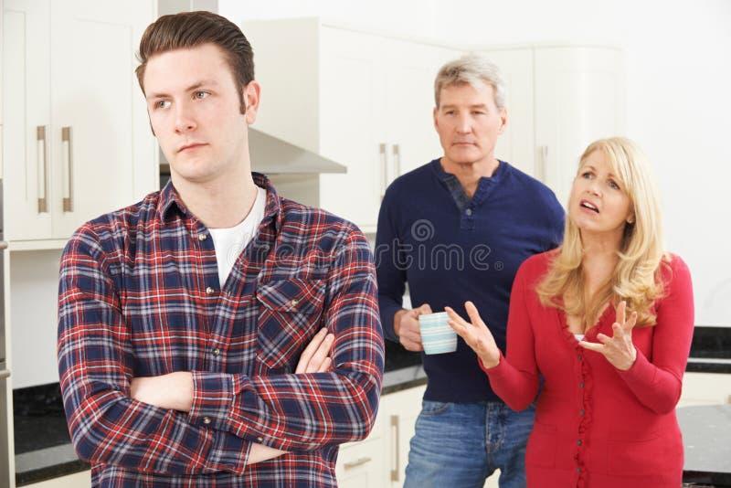Reife Eltern frustriert mit dem erwachsenen Sohn, der zu Hause lebt stockfotografie