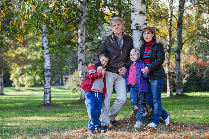 Reife Eltern mit Kindern stehen zusammen im Park, in voller Länge lizenzfreies stockbild