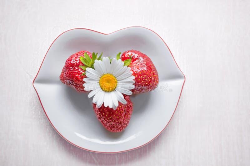 Reife Erdbeere und eine Gänseblümchenblume sind auf einer weißen Platte in Form der Lippen auf einem hellen hölzernen Hintergrund lizenzfreie stockfotos