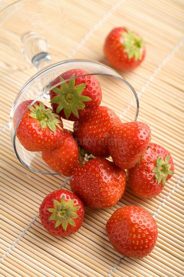Reife Erdbeeren, die von der Schüssel fallen lizenzfreies stockfoto