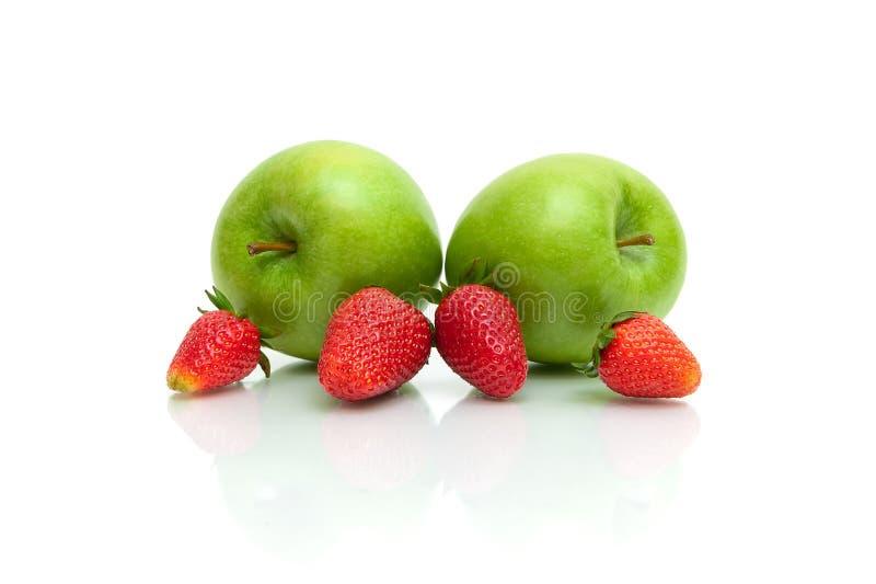 Reife Erdbeeren und grüne Äpfel auf einem weißen Hintergrund lizenzfreies stockfoto