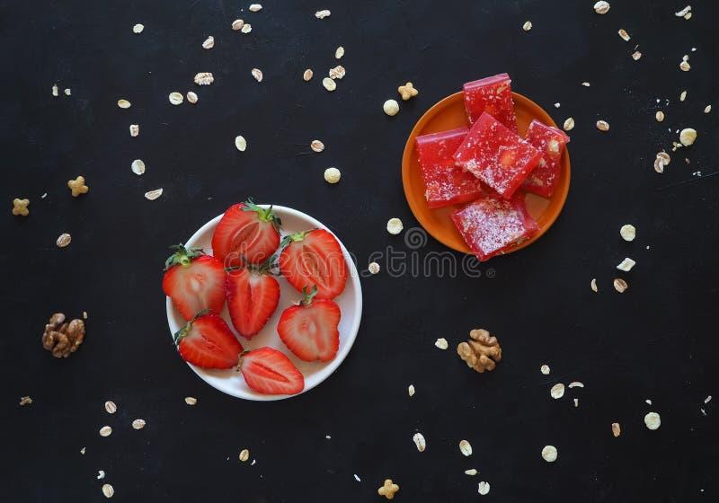 Reife Erdbeeren und türkische Freude auf einer schwarzen Tabelle Beschneidungspfad eingeschlossen lizenzfreie stockfotos