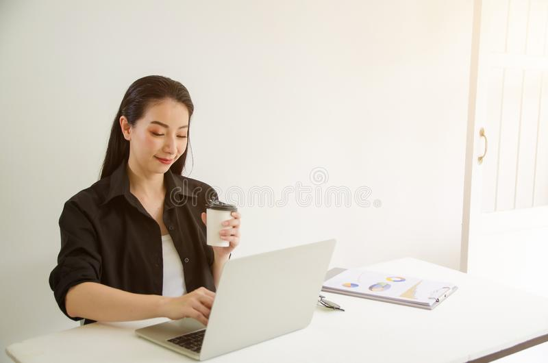Reife erfolgreiche Geschäftsfrau, die Laptop während zu Hause im Büroarbeitsplatz betrachtet stockbild