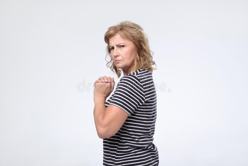 Reife europäische Frau versteckt etwas in ihren Händen und in Blicken vorsichtig vorwärts stockfotografie