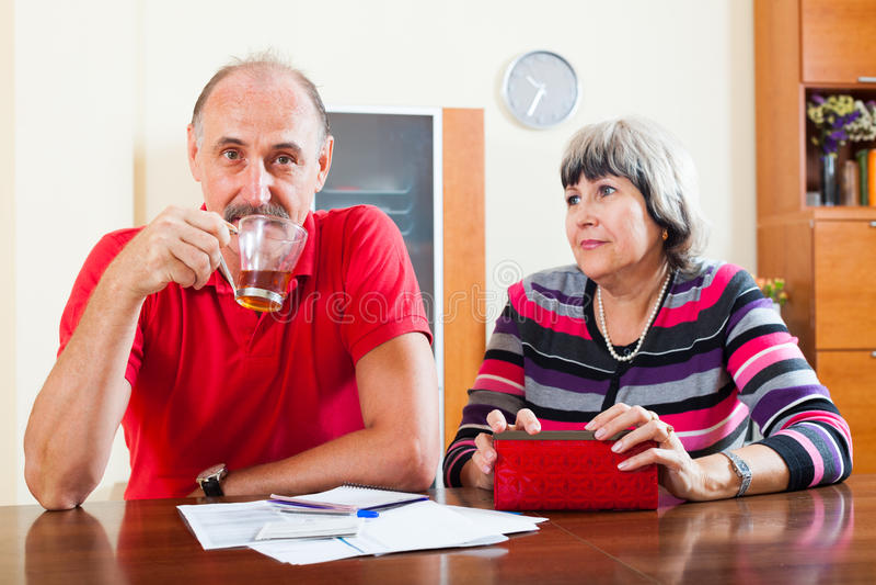 Reife Frau bittet um Geld vom Ehemann lizenzfreies stockfoto