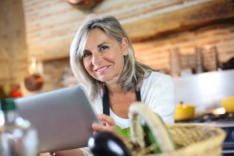 Reife Frau in der Küche unter Verwendung der Tablette bevor dem Kochen lizenzfreies stockbild