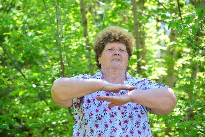 Reife Frau, die Übungen in der Natur tut stockbilder