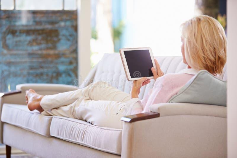 Reife Frau, die auf Sofa At Home Using Digital-Tablet sich entspannt stockfotografie