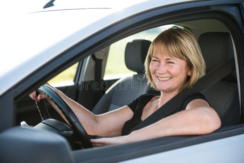 Reife Frau, die Auto fährt lizenzfreie stockfotos