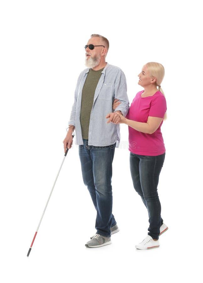 Reife Frau, die blinder Person mit langem Stock hilft lizenzfreie stockfotos
