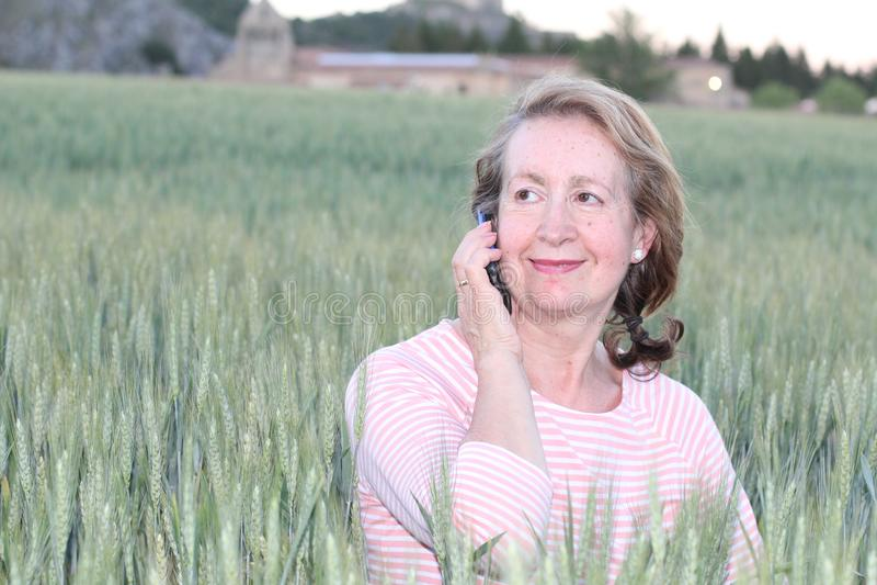 Reife Frau, die durch Mobiltelefon in der Natur nennt lizenzfreies stockfoto