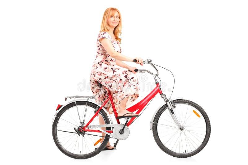 Reife Frau, die ein Fahrrad reitet lizenzfreie stockfotografie