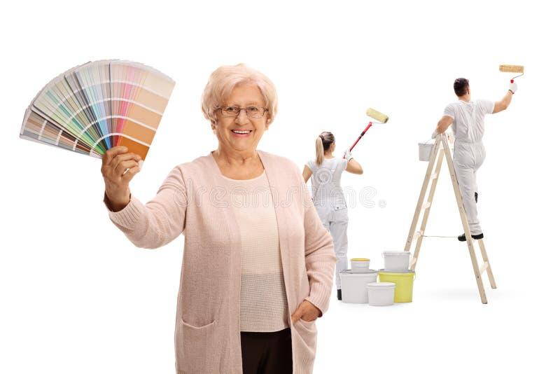 Reife Frau, die ein Farbmuster mit zwei Malern malen b hält lizenzfreies stockbild