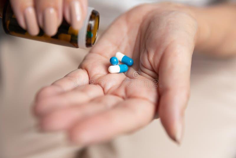Reife Frau, die eine Dosis Tabletten aus Glasflaschen herausnimmt stockfotos