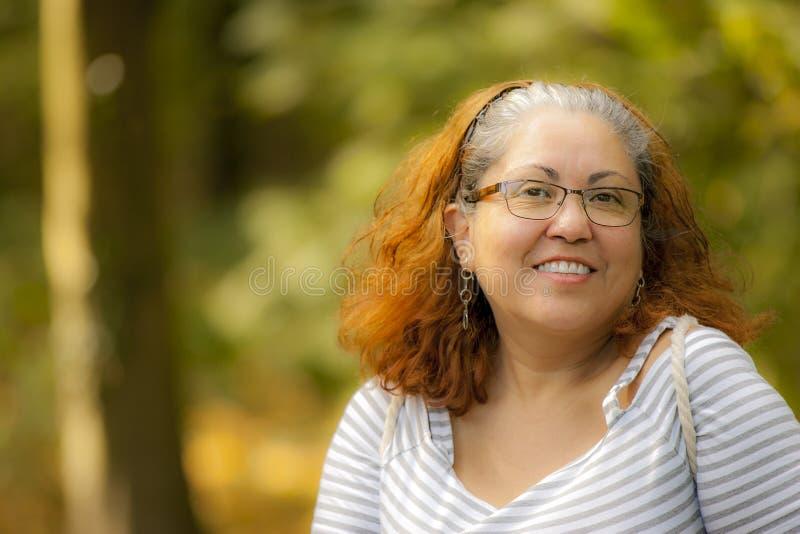 Reife Frau, die an einem wunderbaren und sonnigen Herbsttag lächelt lizenzfreie stockfotografie