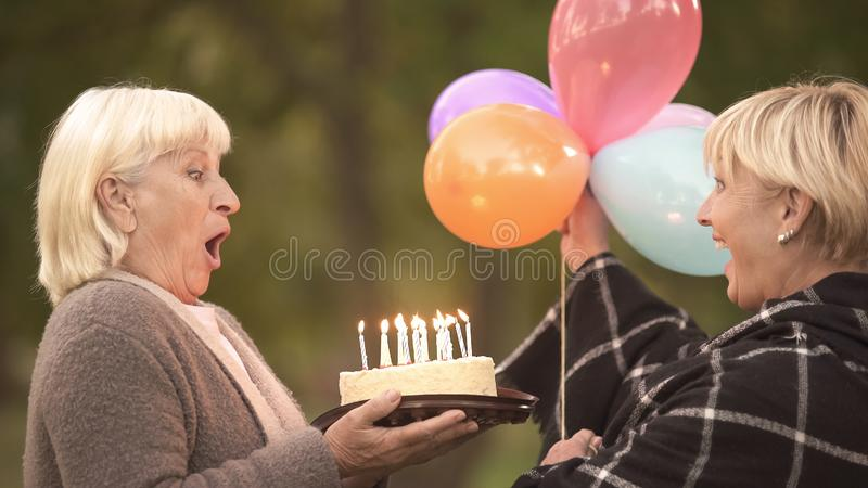 Reife Frau, die geht, Kerzen auf Geburtstagskuchen vom besten Freund heraus durchzubrennen stockfotografie