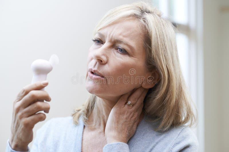 Reife Frau, die Hitzewallung von der Menopause erfährt stockbild